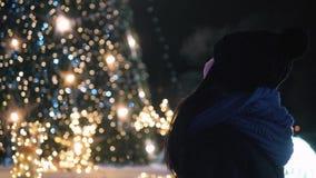 Mulher atrativa nova que está na frente da árvore de Natal brilhante Mulher na roupa morna fora na noite que olha filme