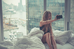 Mulher atrativa nova que faz o autorretrato na cama na manhã Fotos de Stock