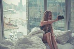 Mulher atrativa nova que faz o autorretrato na cama na manhã Fotografia de Stock