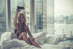 Mulher atrativa nova que faz o autorretrato na cama na manhã Imagens de Stock Royalty Free