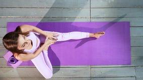 Mulher atrativa nova que faz o esticão na esteira da ioga Vista superior filme
