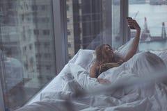 Mulher atrativa nova que faz o selfie na cama Fotografia de Stock