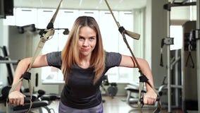 Mulher atrativa nova que faz o treinamento do crossfit do Abs do núcleo com as correias da aptidão no gym TRX video estoque