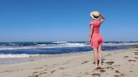 Mulher atrativa nova que guarda seu chapéu e que veste o vestido vermelho que olha o mar e o horizonte tormentosos O vestido verm video estoque