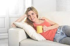 Mulher atrativa nova que mantém a xícara de café que senta-se no sorriso do sofá do sofá em casa feliz imagens de stock