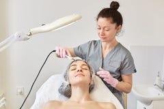 Mulher atrativa nova que obtém o tratamento de limpeza da pele facial ultrassônica pelo cosmetologist profissional, no salão de b fotografia de stock