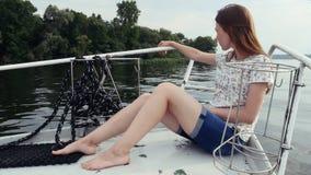 Mulher atrativa nova que relaxa no iate da navigação Cruzeiro de viagem da menina no barco video estoque