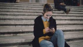 Mulher atrativa nova que senta-se na escada na cidade e no smartphone do uso Menina do estudante que texting com amigos fotos de stock royalty free
