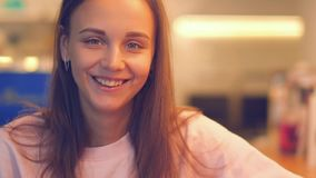 Mulher atrativa nova que sorri à câmera no café vídeos de arquivo