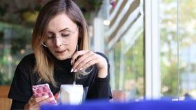 Mulher atrativa nova que sorri à câmera no café video estoque