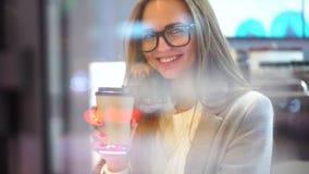 Mulher atrativa nova que sorri à câmera no café Café bebendo da menina feliz e relaxamento no café, no sorriso e na vista filme