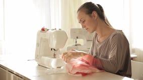 Mulher atrativa nova que trabalha na máquina de costura vídeos de arquivo