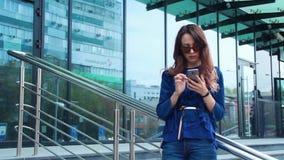 Mulher atrativa nova que usa o smartphone no centro da cidade, conceito moderno urbano video estoque