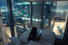 Mulher atrativa nova que usa o telefone celular na cama Fotos de Stock