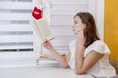 A mulher atrativa nova senta-se pelo tablenand lê o livro em casa foto de stock royalty free