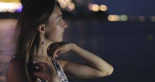 A mulher atrativa olha o mar na noite video estoque