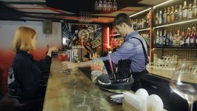 A mulher atrativa que ? serviu cocktail na barra Barman que faz o cocktail ao convidado vídeos de arquivo