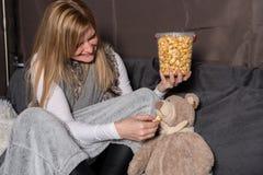 Mulher atrativa que alimenta sua peluche com pipoca Fotos de Stock