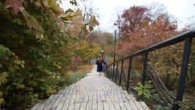 Mulher atrativa que anda em baixo no parque do outono filme