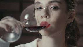 Mulher atrativa que bebe o vinho da uva vermelha do vidro Vinho tinto bebendo da senhora vídeos de arquivo