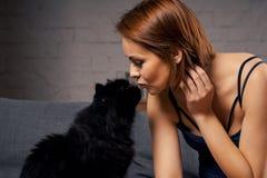 Mulher atrativa que beija um gato preto Fotografia de Stock