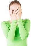 Mulher atrativa que cobre sua cara com ambas as mãos. Imagens de Stock
