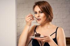 Mulher atrativa que come o bolo de chocolate no sofá Imagens de Stock Royalty Free