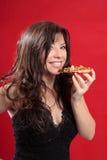 Mulher atrativa que come a pizza imagem de stock
