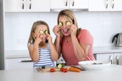 Mulher atrativa que cozinha junto com seus 6 ou 7 anos pequenos louros bonitos doces brincalhão feliz da filha idosa com o pepino Fotos de Stock
