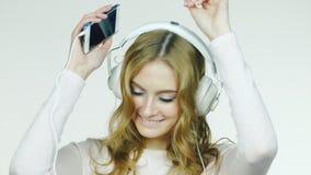 Mulher atrativa que dança e que escuta a música Tiro video no estúdio em um fundo branco filme