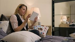 Mulher atrativa que encontra-se na cama usando a tabuleta digital Foto de Stock