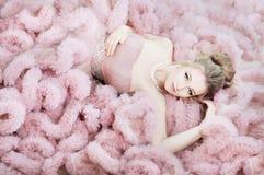 Mulher atrativa que encontra-se no assoalho no vestido cor-de-rosa da nuvem Forma fotografia de stock royalty free