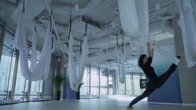Mulher atrativa que estica seus pés usando a rede da ioga no fitness center com a grande janela do chão ao teto muitos video estoque