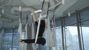 Mulher atrativa que estica seus pés usando a rede da ioga no fitness center com a grande janela do chão ao teto muitos vídeos de arquivo