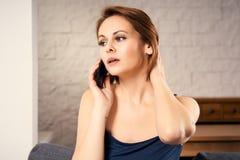 A mulher atrativa que fala no telefone e mantém seu cabelo disponivel Fotografia de Stock Royalty Free