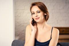 Mulher atrativa que fala no telefone no sofá Foto de Stock Royalty Free