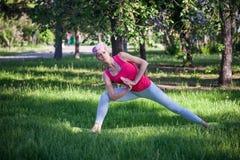 Mulher atrativa que faz a ioga no parque, estilo de vida ativo O conceito de um estilo de vida saudável e de uma recreação ativa Imagens de Stock