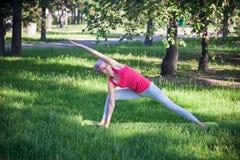Mulher atrativa que faz a ioga no parque, estilo de vida ativo O conceito de um estilo de vida saudável e de uma recreação ativa Fotos de Stock Royalty Free