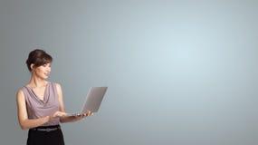 Mulher atrativa que guarda um portátil com espaço da cópia Imagens de Stock