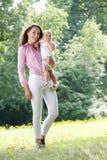 Mulher atrativa que guardara o bebê fora imagem de stock royalty free