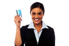 Mulher atrativa que indica seu cartão de crédito Foto de Stock Royalty Free