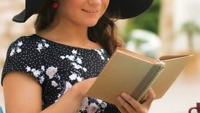 Mulher atrativa que lê café novo interessante do livro, apreciando férias, close up video estoque