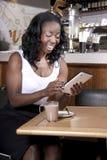 Mulher atrativa que lê sua mensagem em uma tabuleta Imagens de Stock Royalty Free