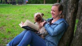 Mulher atrativa que lê um livro em um parque por uma árvore Corridas bonitos de um cão a ela vídeos de arquivo