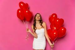 Mulher atrativa que levanta na câmera com balões vermelhos fotografia de stock royalty free