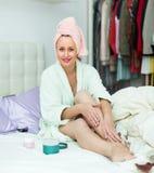 Mulher atrativa que põe o creme sobre os pés Fotos de Stock Royalty Free