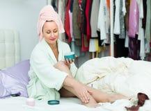 Mulher atrativa que põe o creme sobre os pés Fotografia de Stock Royalty Free