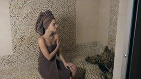 Mulher atrativa que relaxa em um hammam - banho de vapor turco com o azulejo no estilo romano vídeos de arquivo
