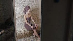 Mulher atrativa que relaxa em um hammam - banho de vapor turco com o azulejo no estilo romano video estoque