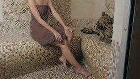 Mulher atrativa que relaxa em um hammam - banho de vapor turco com o azulejo no estilo romano filme